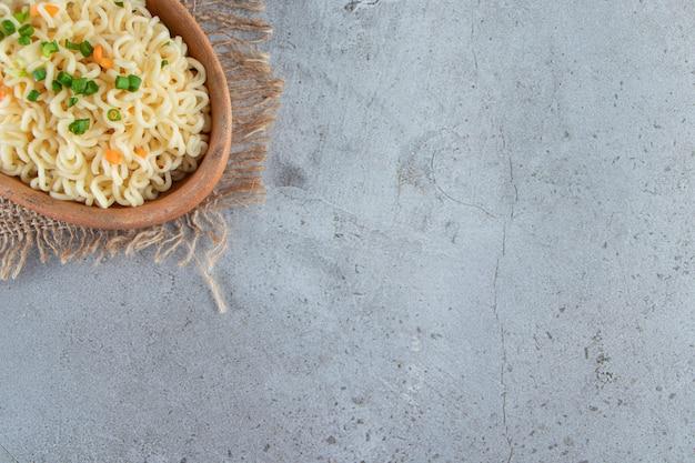 Noodle in een kom op een jute naast groenten, op de marmeren achtergrond.