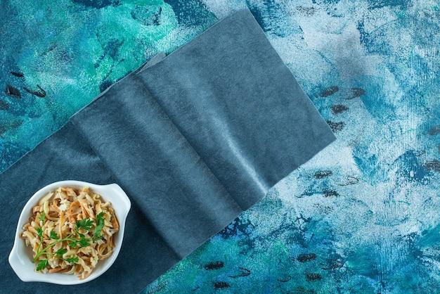 Noodle in een kom op een stuk stof, op de blauwe tafel.