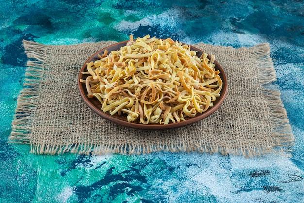 Noodle in een kom op een textuur, op de blauwe tafel.