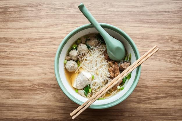 Noodle soep varkensvlees gehaktbal en tofu in kom met chopstick