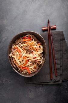 Noodles in een glazen kom met groenten en rundvlees.