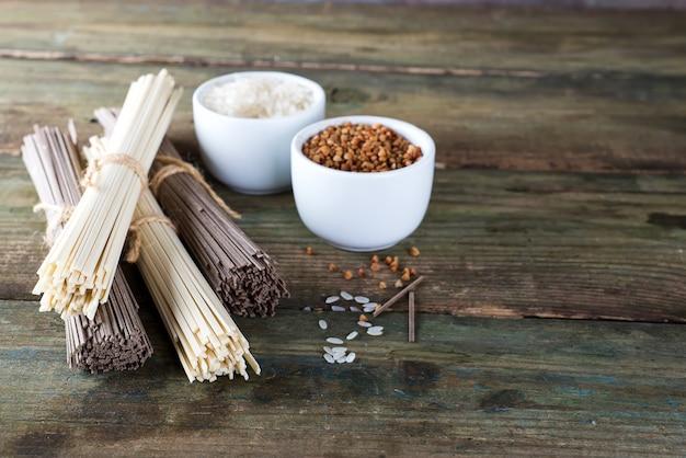 Noodles soba en sommel, kommen met boekweit en rijst op een oude houten achtergrond