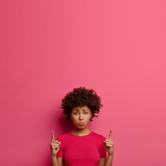 Noodlijdende, ellendige vrouw wijst naar boven en kijkt ongewild, ontevreden over prijzen, toont kopie ruimte voor advertenties, staat tegen roze muur, toont iets buitengewoons