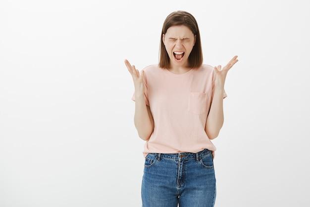 Noodlijdende en beu jonge vrouw die zich gestrest voelt, schreeuwend van streek