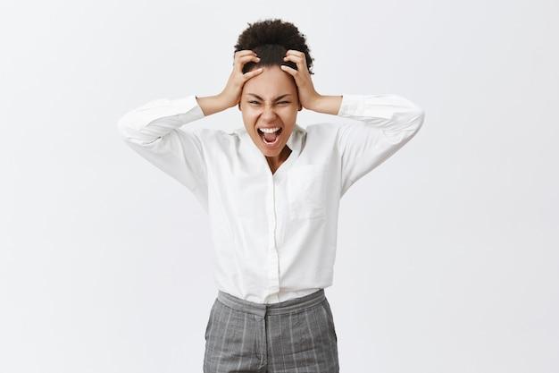 Noodlijdende en pissige boze vrouw met een donkere huidskleur schreeuwde en scheurde haar op het hoofd