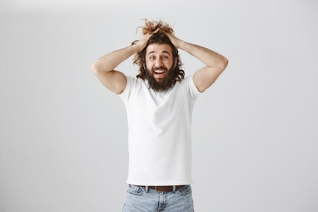 Noodlijdende gefrustreerde man uit het midden-oosten raakt in paniek, grijpt zijn hoofd en trekt een onrustig gezicht