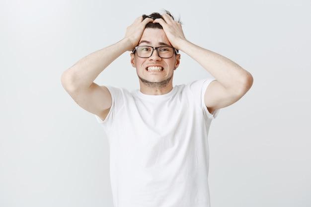 Noodlijdende man in paniek grijpt het hoofd en kijkt angstig