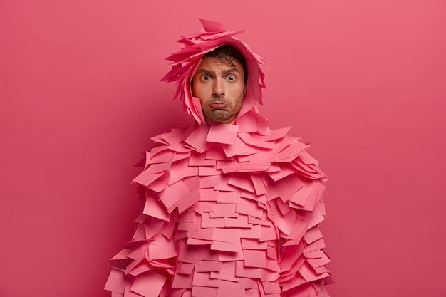 Noodlijdende, ongelukkige man pakt onderlip, kijkt beledigd, draagt kleding gemaakt van zelfklevende briefjes, poseert tegen roze muur, ontevreden over iets, neerslachtig.