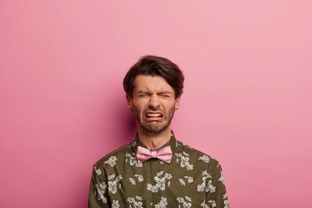Noodlijdende sombere man drukt negatieve emoties uit, draagt een modieus shirt met roze vlinderdas, fronst gezicht van ontevredenheid, huilt van wanhoop