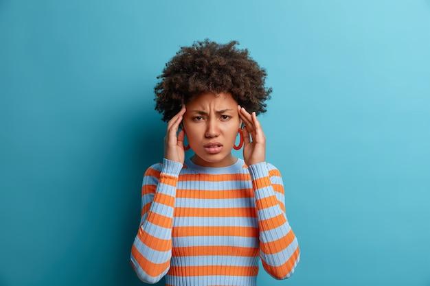 Noodlijdende vrouw met donkere huid raakt tempels en lijdt aan migraine, pijnlijke hoofdpijn, voelt zich duizelig en fronst gezicht, heeft pijnstillers nodig, gekleed in casual gestreepte trui, geïsoleerd op blauwe muur