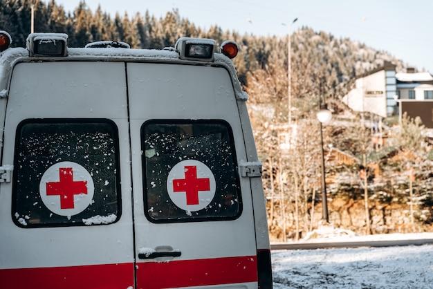 Noodsituatieauto bij het zonnige bos. ambulance staande op de besneeuwde weg in het dorp in de bergen. winterconcept