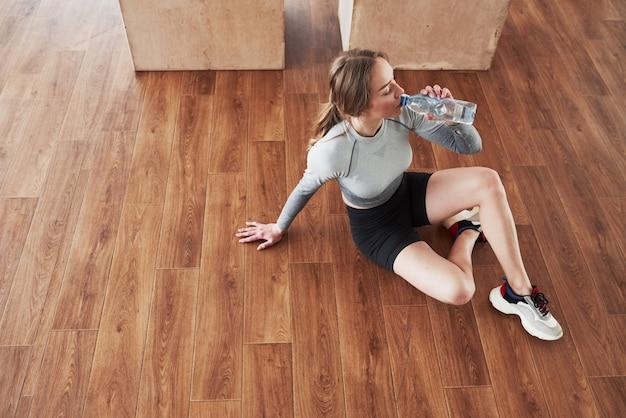 Noodzaak om te rusten en water te drinken. sportieve jonge vrouw heeft fitnessdag in de sportschool in de ochtendtijd