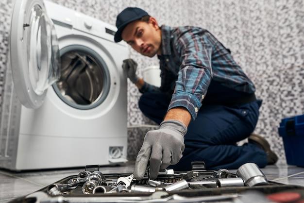 Noodzakelijke dingen zijn altijd bij de hand werkende man loodgieter in badkamer wazig