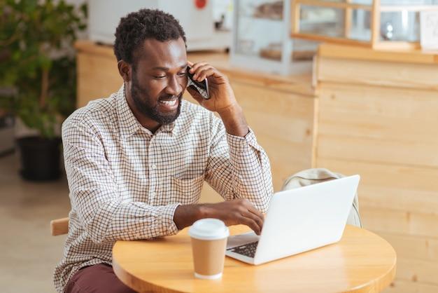 Noodzakelijke discussie. aangename vrolijke man zit aan de tafel in het café, bespreekt werkkwesties aan de telefoon en maakt aantekeningen op de laptop