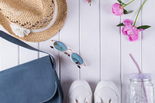 Noodzakelijke zomeraccessoires voor vrouwen op wit oppervlak. bovenaanzicht met kopie ruimte