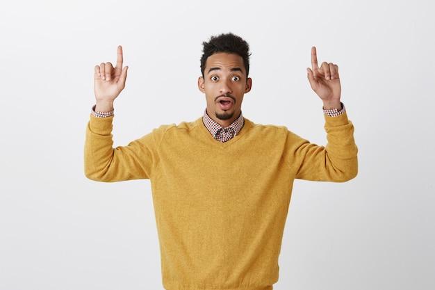 Nooit mooier kopie ruimte gezien. portret van aantrekkelijke emotionele afro-amerikaanse mannelijke student in gele trui wijsvingers opheffen, naar boven wijzend met neergelaten kaak en verbaasde uitdrukking