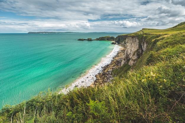 Noord-ierland kustlijn. heldere zee, groen land.