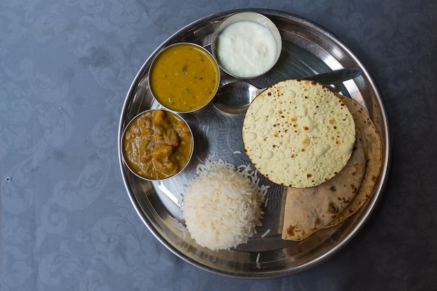 Noord-indiase thali, een typische maaltijd geserveerd op roestvrij stalen plaat op blauwe tafel