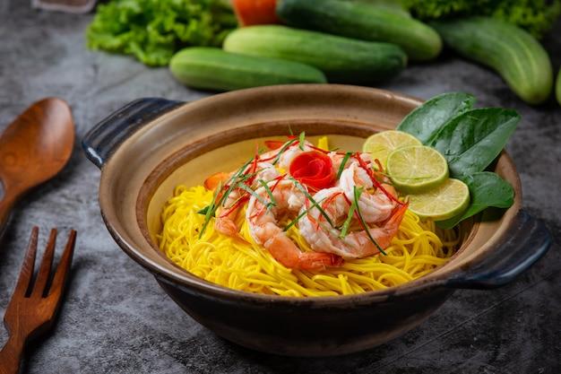 Noord-thais eten (khao soi-garnalen), pittige noedels versierd met ingrediënten.