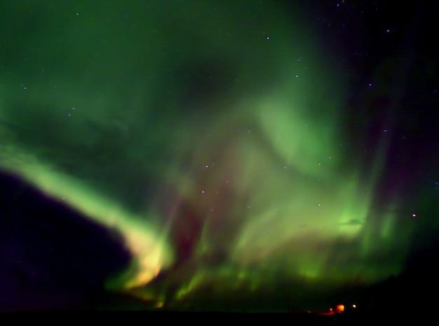 Noordelijke lichten die over het gletsjermeer opvlammen in vatnajokull nationaal park, zuid-ijsland