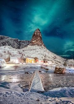 Noordelijke lichten over berg met kleuren skandinavisch dorp in lofoten