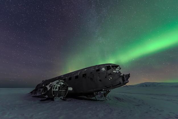 Noordelijke lichtenaurora borealis over vliegtuigschipbreuk in ijsland
