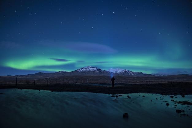 Noorderlicht aan de hemel met een staande man