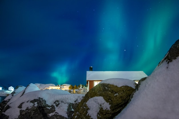 Noorderlicht boven de daken van huizen