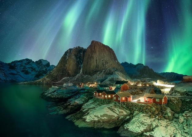 Noorderlicht over vissersdorp met bergketen aan de kust bij hamnoy, lofoten