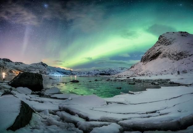 Noorderlichtexplosie op besneeuwde bergketen in de buurt van de kustlijn op de lofoten-eilanden, noorwegen
