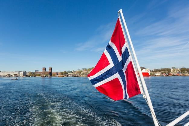 Noorse vlag die op achterschip van een boot in oslo golft