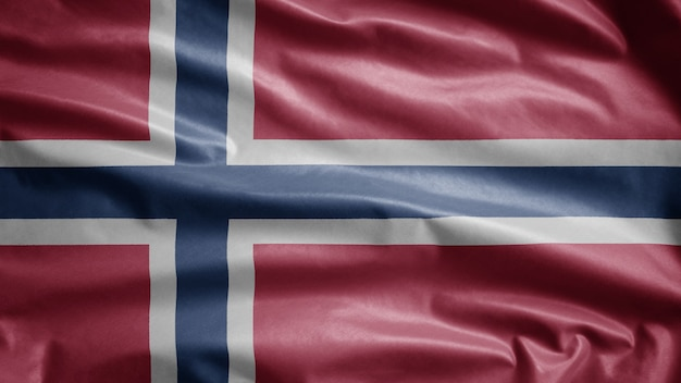 Noorse vlag wappert in de wind. close-up van noorwegen sjabloon blazen, zachte en gladde zijde. doek stof textuur ensign achtergrond