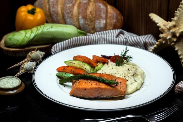 Noorse zalm en aardappelpuree geserveerd met gekookte groenten