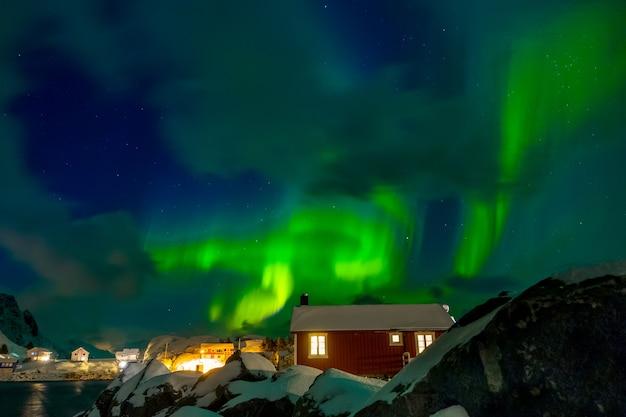 Noorwegen. lofoten. hamnoya stad. winter nacht. aurora borealis boven de daken van huizen