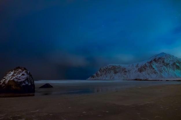 Noorwegen. lofoten. winter nacht. met sneeuw bedekte bergen en zandstrand aan de oceaan