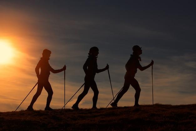 Nordic walking in silhouet bij zonsondergang