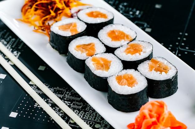 Nori sushi rolt met zalm geserveerd met gember wasabi en geraspte wortel