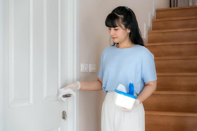 Normaal schot van een aziatische vrouw die de deurknoppen desinfecteert door desinfecterende wegwerpdoekjes uit doos. voorkom het virus en de bacteriën, voorkom covid-19