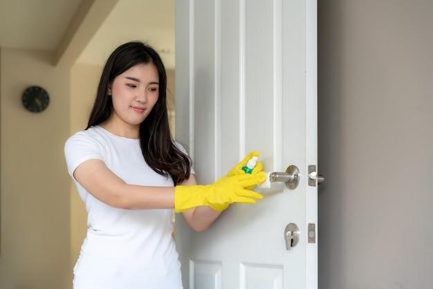 Normaal schot van een aziatische vrouw die de deurknoppen desinfecteert door een blauw ontsmettingsmiddel van een fles te bespuiten.
