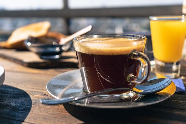 Normale weergave van een kopje zwarte koffie op de voorgrond, met een sinaasappelsap en wat toast erachter.