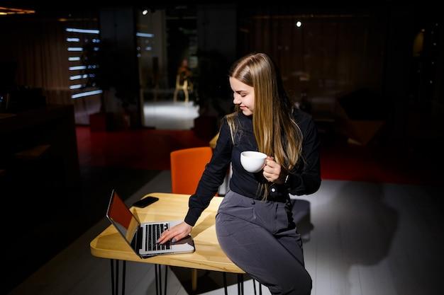Normale werkdag van moderne vrouw zakenman. mooie jonge vrouw die een kopje koffie vasthoudt terwijl ze op haar werkplek zit
