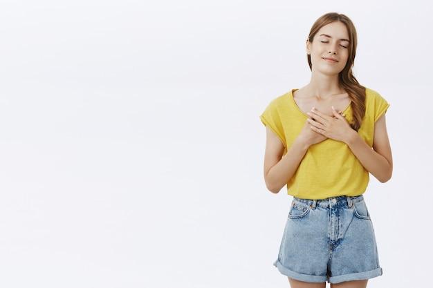 Nostalgisch gelukkig schattig meisje lachend met gesloten ogen en handen op hart