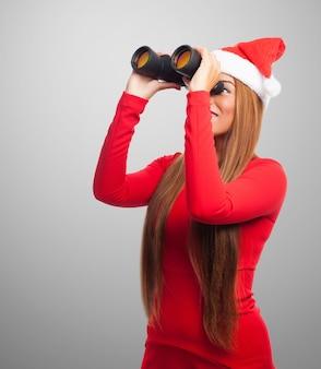 Nosy jonge vrouw met behulp van een verrekijker