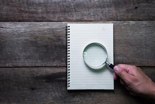 Notaboek en magnifier op houten lijst