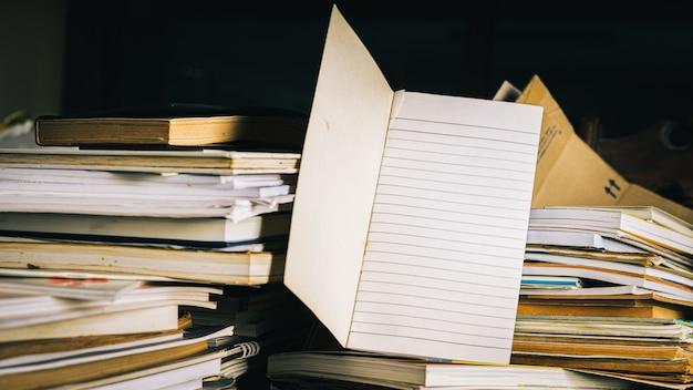 Notaboek met stapel oude boeken op houten lijst.