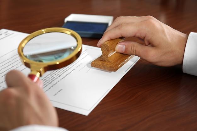 Notaris met behulp van stempel en vergrootglas, close-up