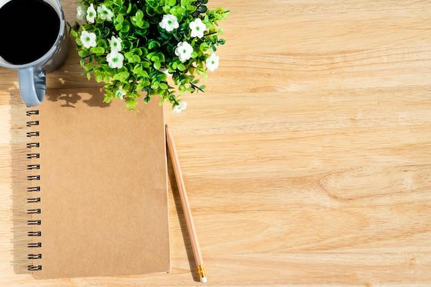 Notebook, bloempot boom, een potlood en een koffiekopje op houten achtergrond, bovenaanzicht met office tafel.