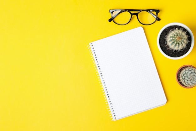 Notebook, bril en cactussen op gele achtergrond, bovenaanzicht