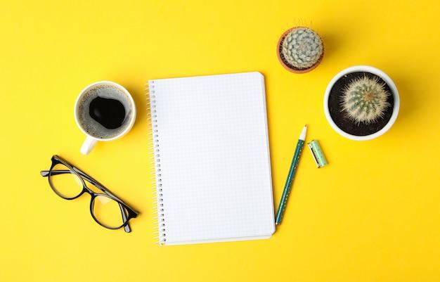 Notebook, bril, koffie, pen en cactussen op gele ondergrond
