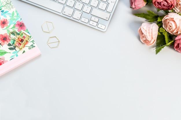 Notebook, een wit toetsenbord en roze rozen op een wit oppervlak